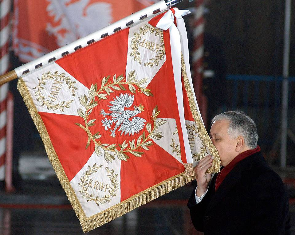File photo shows newly sworn-in Polish President Kaczynski kissing the Polish Army colours as he takes command of the Polish Armed Forces in Warsaw